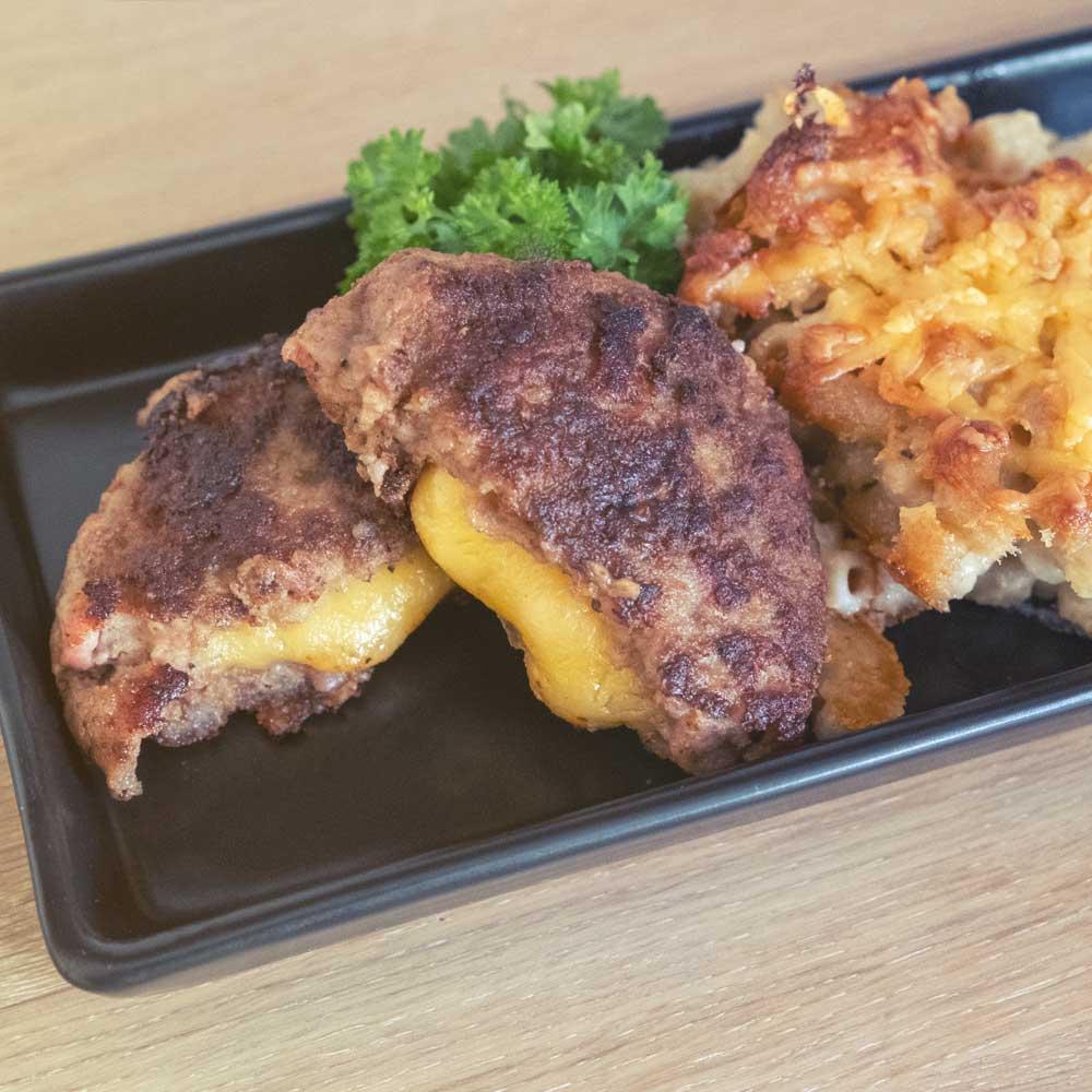 mac and cheese, eli juustomakaroni ja cheddar-täytteiset pekoni-jauhelihapihvit -annoskuva
